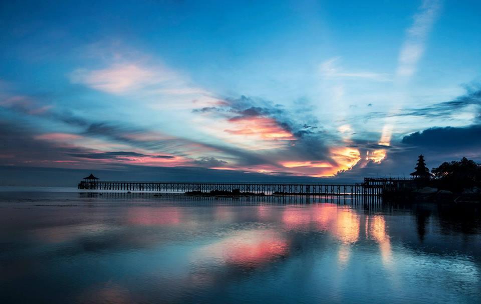 Matahari terbenam dilihat dari dermaga Turi Beach Resort.