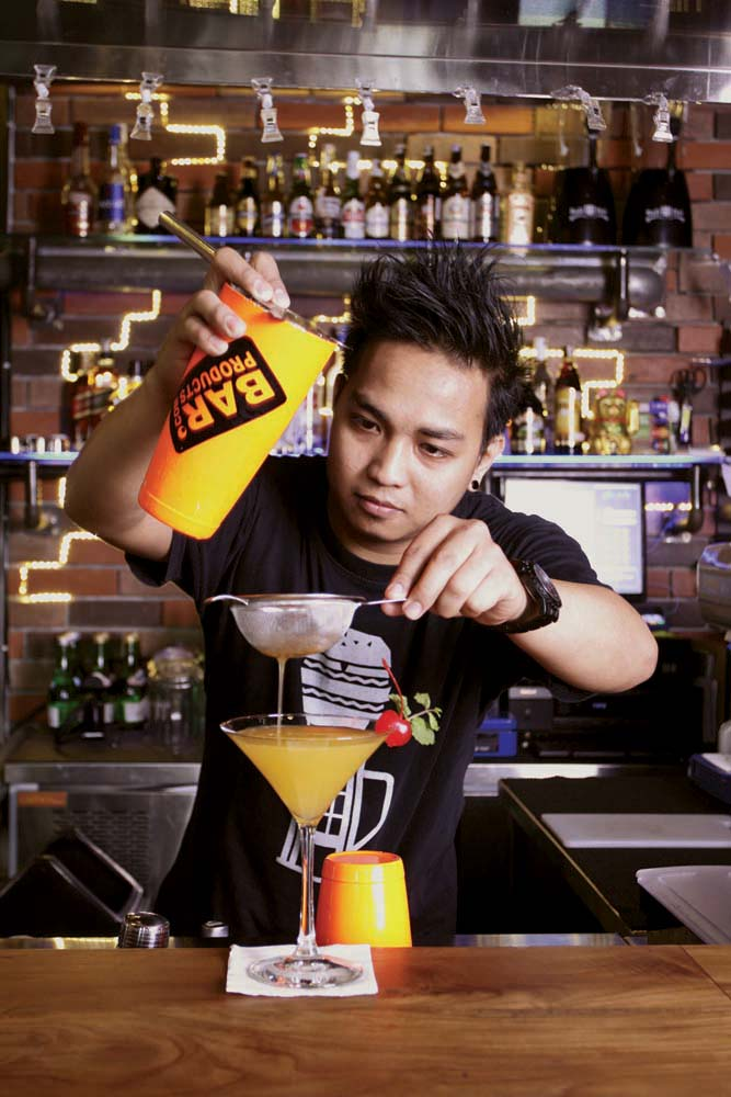 Bartender di YOLO Public House sedang meracik minuman.