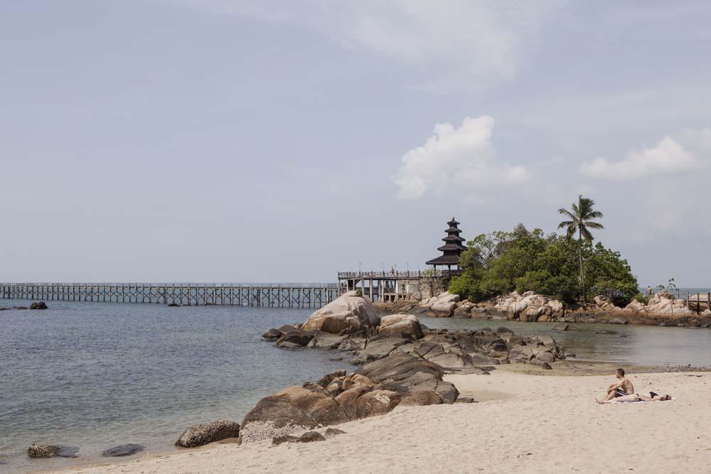 Dua orang turis berjemur di pantai Nongsa.