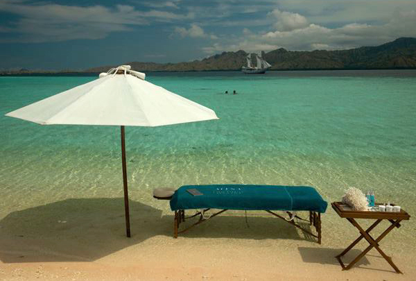 Sesi pijat privat di pantai dengan air laut berwarna turkois.