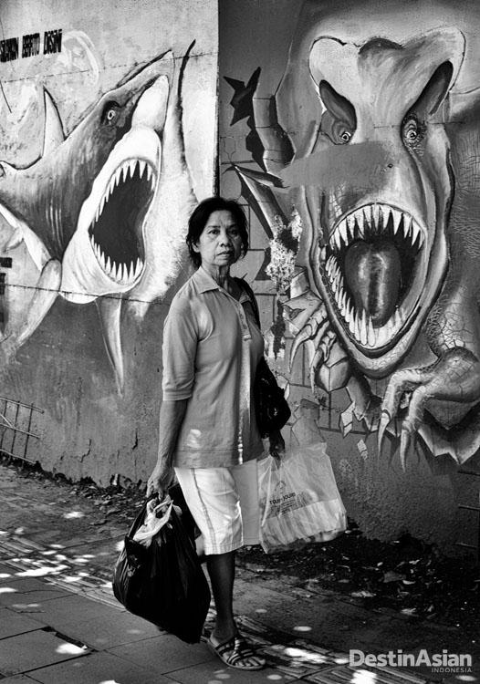 Seorang ibu berjalan melewati tembok bergambar mural di dekat Glodok.