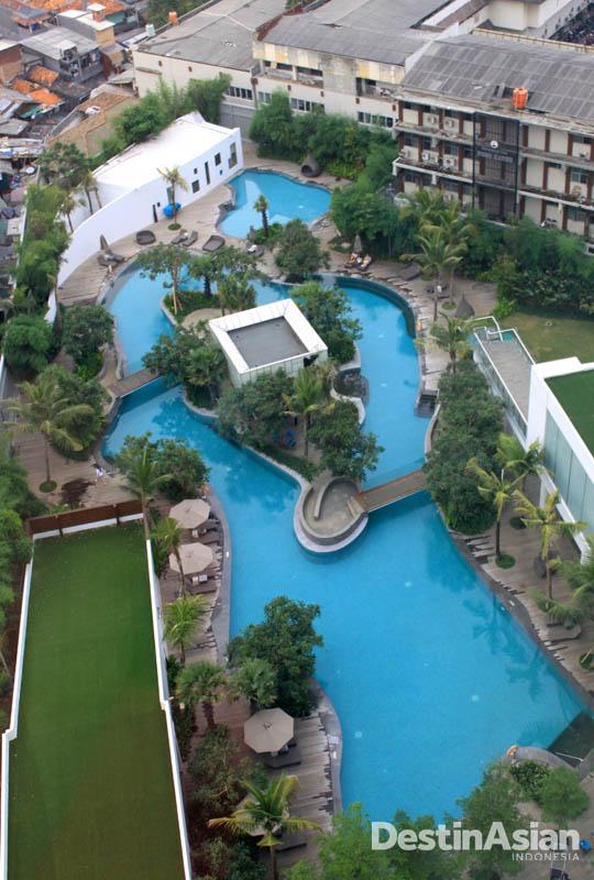 Kolam renang berbentuk laguna luas beserta taman hijau. Cocok untuk bersantai.