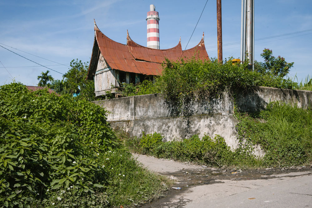 Rumah adat Minangkabau tak berpenghuni di Talawi. Di dekatnya, berdiri pabrik batu bara.