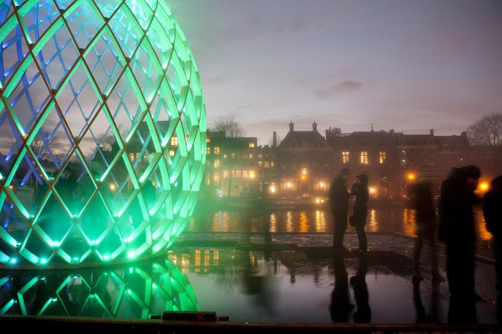 Penduduk kota di sebelah instalasi berjudul OVO karya keroyokan sejumlah seniman. Lampu instalasi tersebut bisa berubah-ubah warnanya. (Foto: Janus Van Den Eijnden)