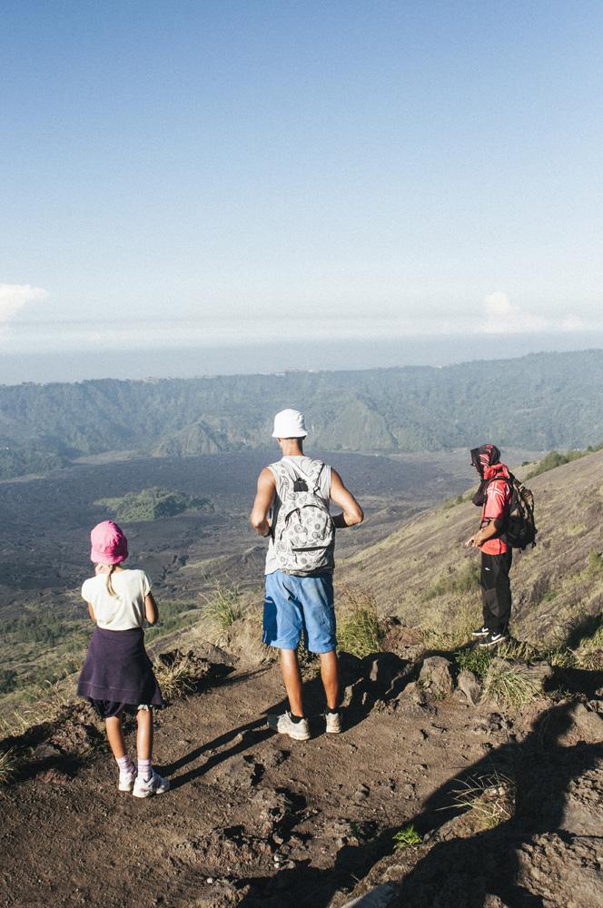 Sekeluarga turis asing tengah menikmati pemandangan di Gunung Batur.