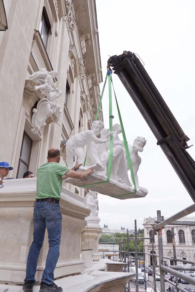 Pekerja memasang patung di gerbang utama.