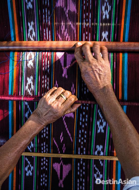 Di samping rumahnya, seorang Ibu menenun kain bermotif manta.