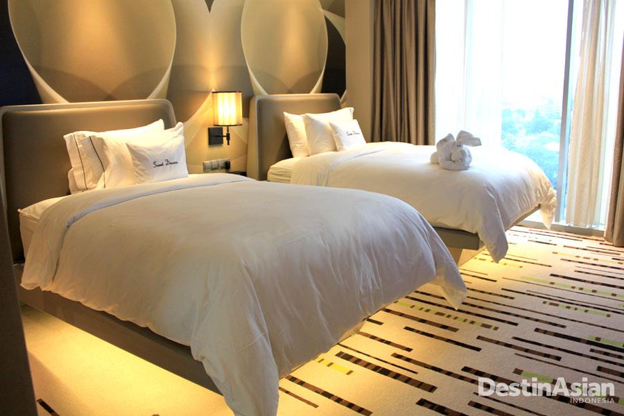 Kamar tipe Deluxe Twin dengan gaya retro dan matras yang terlihat seakan melayang.
