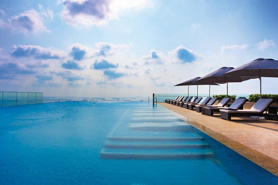 Kolam renang Westin Singapura dengan pemandangan lanskap kota dan laut.